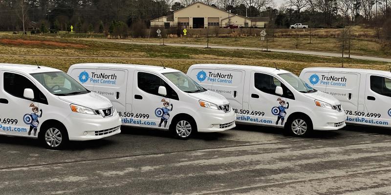 four white TruNorth pest control vans